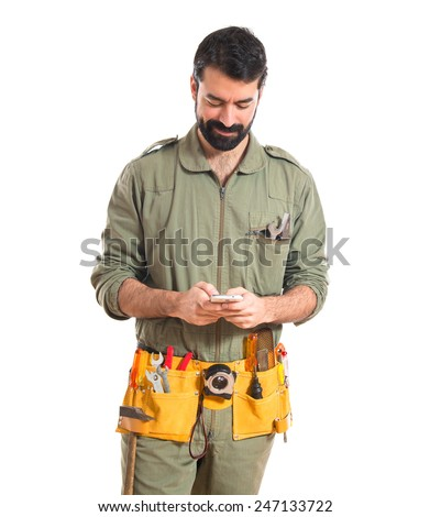 Happy mechanic talking to mobile  - stock photo