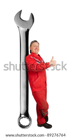 Happy mechanic with big spanner showing ok gesture - stock photo