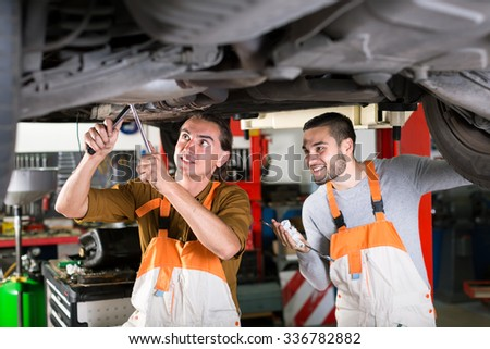 Happy mechanics repairing exhaust system on a lifted up sedan car in a car repair shop - stock photo