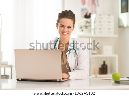 Happy medical doctor woman working on laptop - stock photo