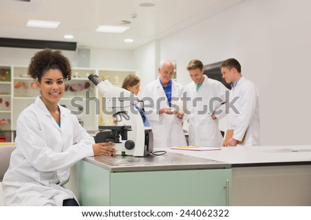 Happy medical student working with microscope at the university - stock photo