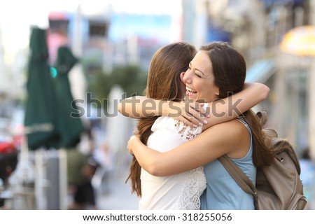 Happy meeting of two friends hugging in the street - stock photo