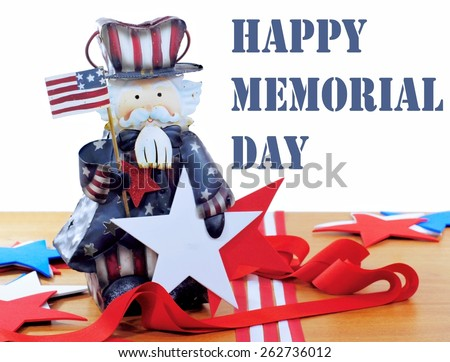 Happy Memorial Day message image in red, white and blue. A cute Uncle Sam figurine is surrounded by stars and strips with ribbons and cutouts on a wood table. Text is removable. Background is white. - stock photo