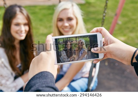 happy memories of girl friends being captured by mobile cell phone camera outdoors - stock photo