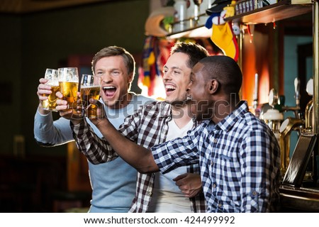 Happy men with beer in pub - stock photo
