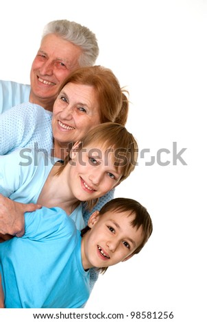 Happy mercy grandparents with grandchildren fooled on a light background - stock photo