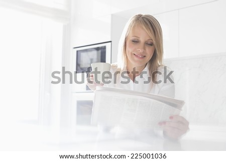 Happy mid adult businesswoman having coffee while reading newspaper at home - stock photo