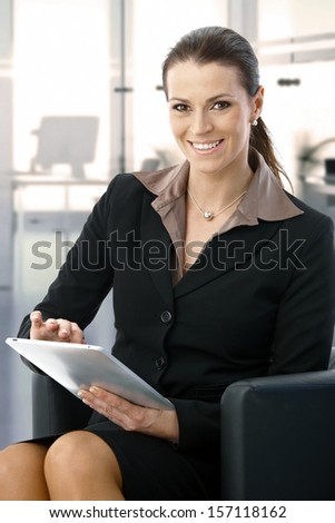 Happy mid-adult businesswoman sitting in armchair at office working with tablet, smiling. - stock photo
