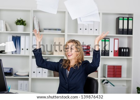 Happy mid adult businesswoman throwing documents in office