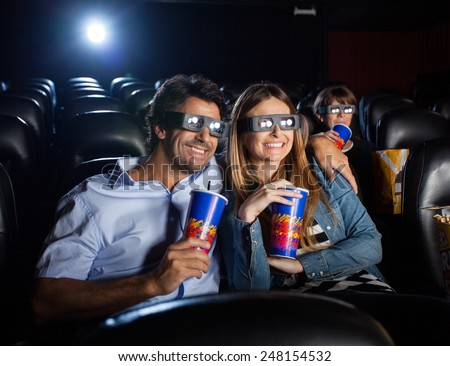 Happy mid adult couple having drinks while watching 3D movie in cinema theater - stock photo