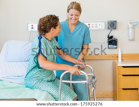 Happy mid adult nurse assisting female patient using walking frame in hospital - stock photo