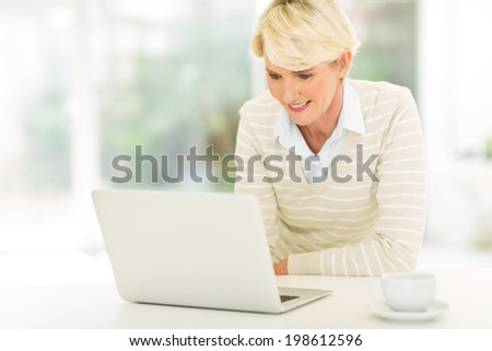 happy mid age woman using laptop computer at home - stock photo