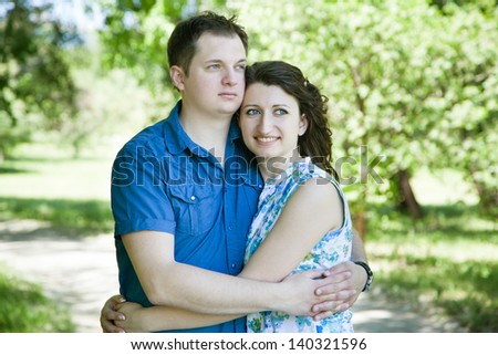 happy middle-age couple in park looking ahead - stock photo