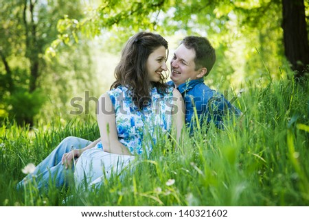 Happy middle-age couple laughing sitting in green grass outdoors