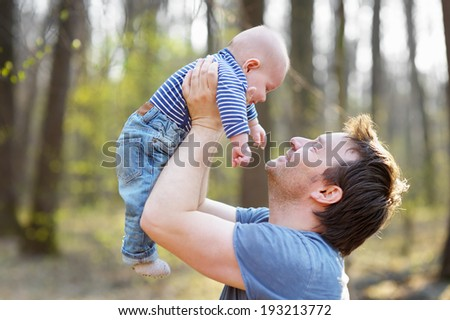 Happy middle age man holding his little baby  - stock photo