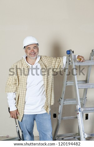 Happy middle age man standing near ladder over colored background