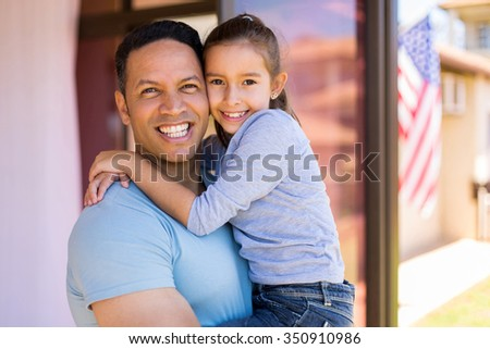 happy middle aged american man holding his daughter outside their house - stock photo