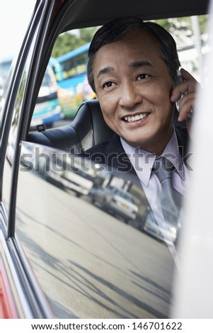 Happy middle aged businessman using cell phone in car - stock photo