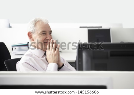 Happy middle aged businessman with hands clasped sitting at computer desk - stock photo