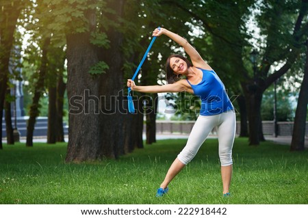 Happy middle aged caucasian brunette woman in blue sportswear stretching with blue jumping rope over her head outdoors smiling - stock photo