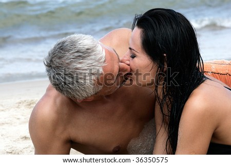 Happy middle aged couple kissing on the beach, enjoying their summer holiday together. - stock photo
