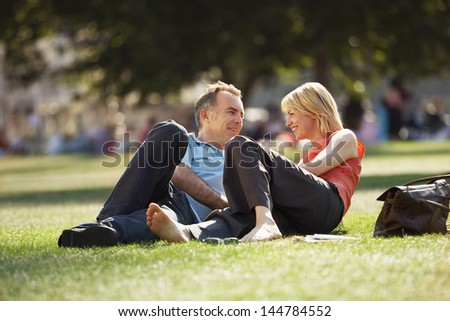 Happy middle aged couple reclining in a park - stock photo