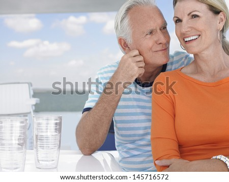 Happy middle aged couple spending time together on motorboat - stock photo