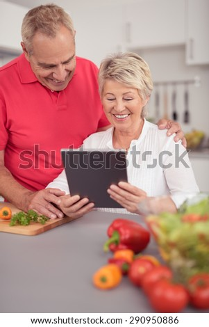 Happy Middle Aged Couple Watching Something on Tablet Computer While Preparing for Dinner at the Kitchen. - stock photo