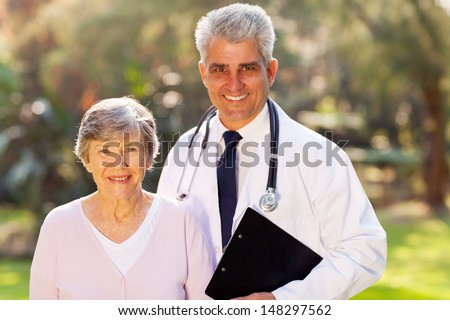 happy middle aged doctor and senior patient outdoors - stock photo