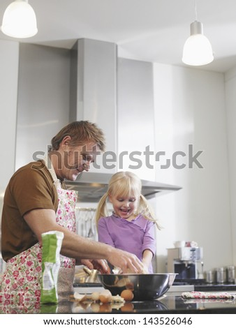 Happy middle aged father and daughter baking in kitchen