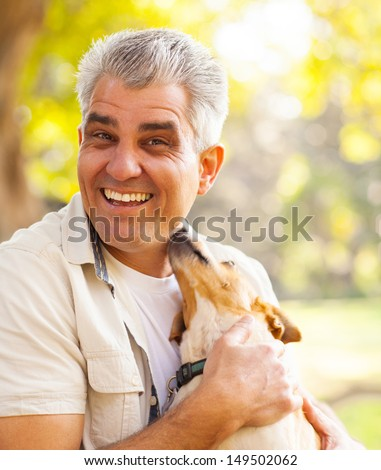 happy middle aged man and pet dog outdoors - stock photo