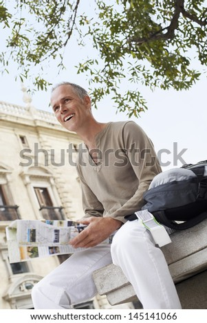 Happy middle aged man holding map in front of building - stock photo