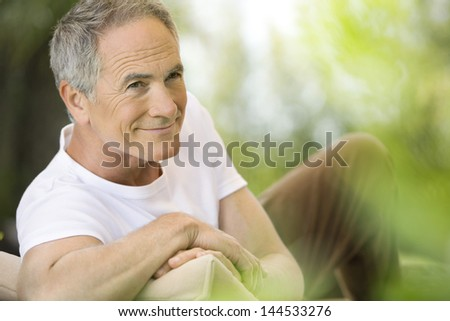 Happy middle aged man reclining on deck chair in garden - stock photo