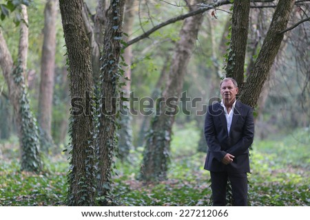 Happy middle aged man reclining on deck chair in garden. Handsome unshaven middle age man in an outdoor setting.  - stock photo