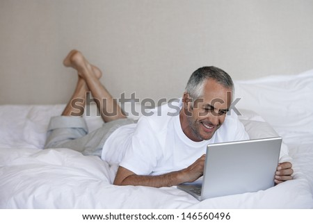 Happy middle aged man using laptop while lying in bed at home