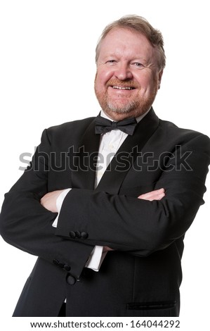 Happy middle aged man wearing tuxedo, arms crossed, isolated on white