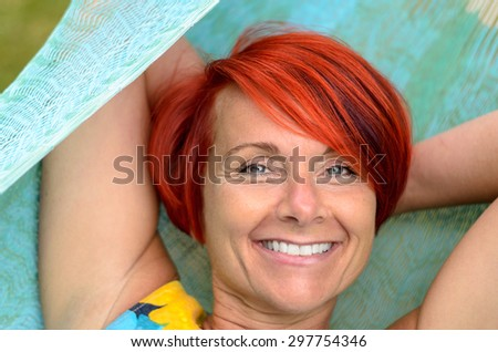 Happy Middle Aged Redhead Woman Smiling at the Camera While Relaxing on Hammock at the Garden - stock photo