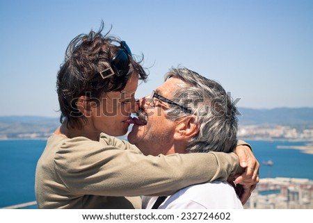 Happy middle aged woman and senior man in love kissing outdoors.