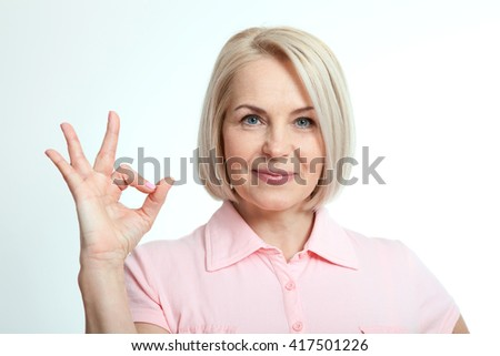Happy middle-aged woman showing okay, ok, good results, success sign hand. Portrait close up isolated over white background.