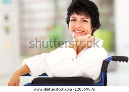 happy middle aged woman sitting on wheelchair and recovering from sickness - stock photo
