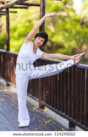 happy middle aged woman stretching outdoors - stock photo