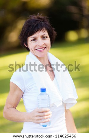 happy middle aged woman with bottle of water after exercise - stock photo