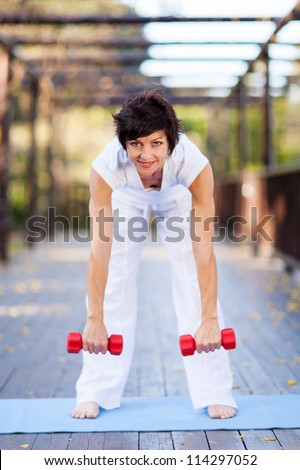 happy middle aged woman working out with dumbbells - stock photo
