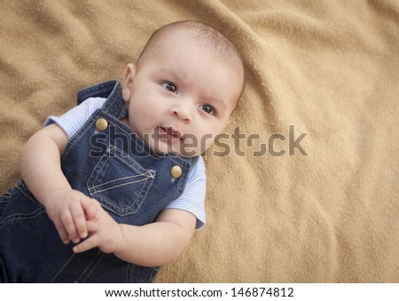 Happy Mixed Race Baby Boy Laying on Blanket. - stock photo