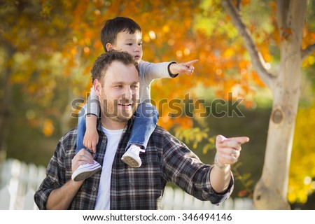 Happy Mixed Race Boy Riding Piggyback and Pointing on Shoulders of Caucasian Father. - stock photo