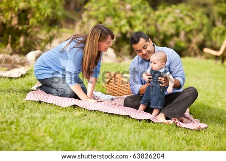 Happy Mixed Race Family Having a Picnic and Playing In The Park. - stock photo