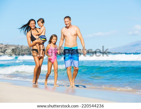 Happy Mixed Race Family of Four on Tropical Sunny Beach - stock photo