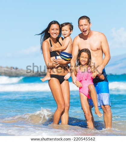 Happy Mixed Race Family of Four Playing and Having Fun on the Beach - stock photo