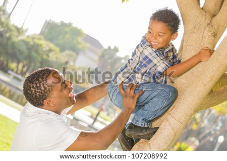 Happy Mixed Race Father Helping Son Climb a Tree in the Park. - stock photo