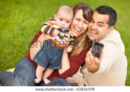 Happy Mixed Race Parents and Baby Boy Taking Self Portraits at the Park. - stock photo